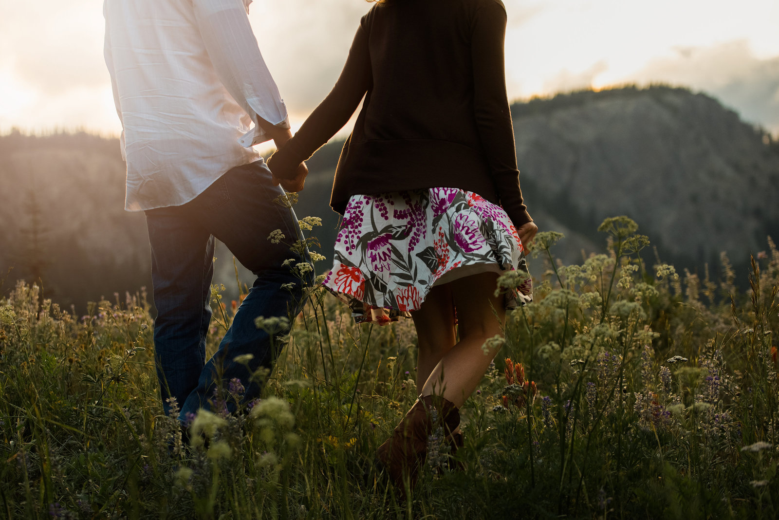Couple walkign through a field of flowers by Roslyn Engagement Photographer
