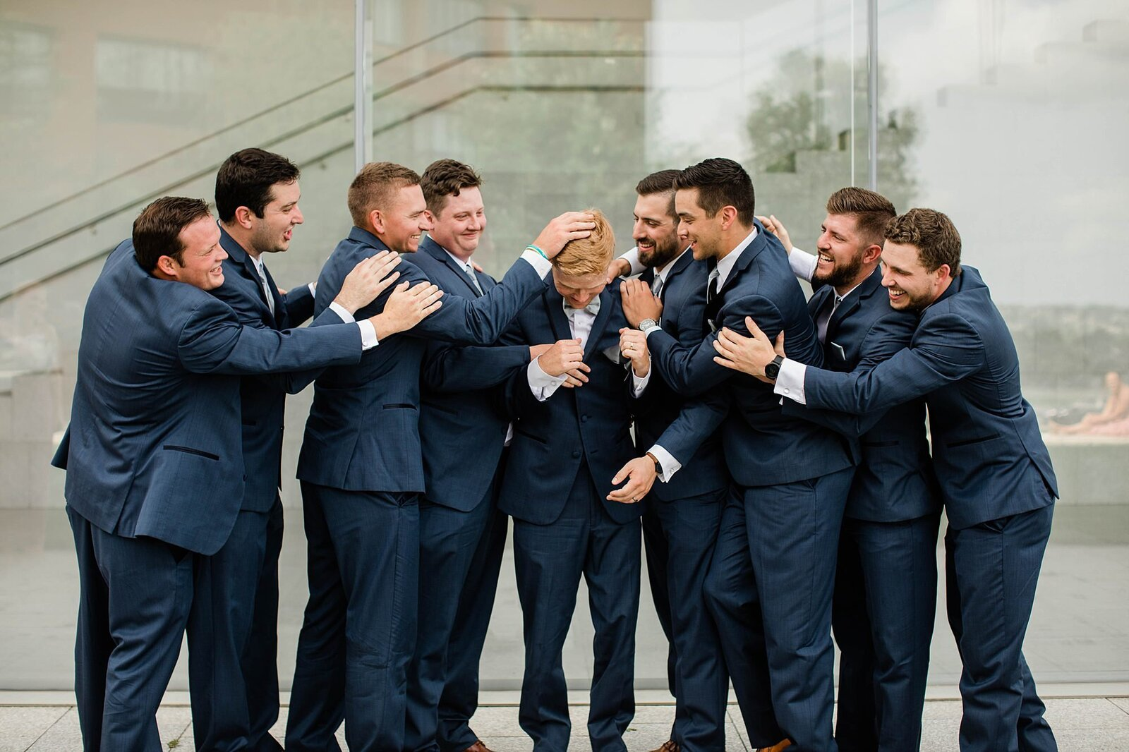 Groom and groomsmen horseplay in front of Nerman Museum