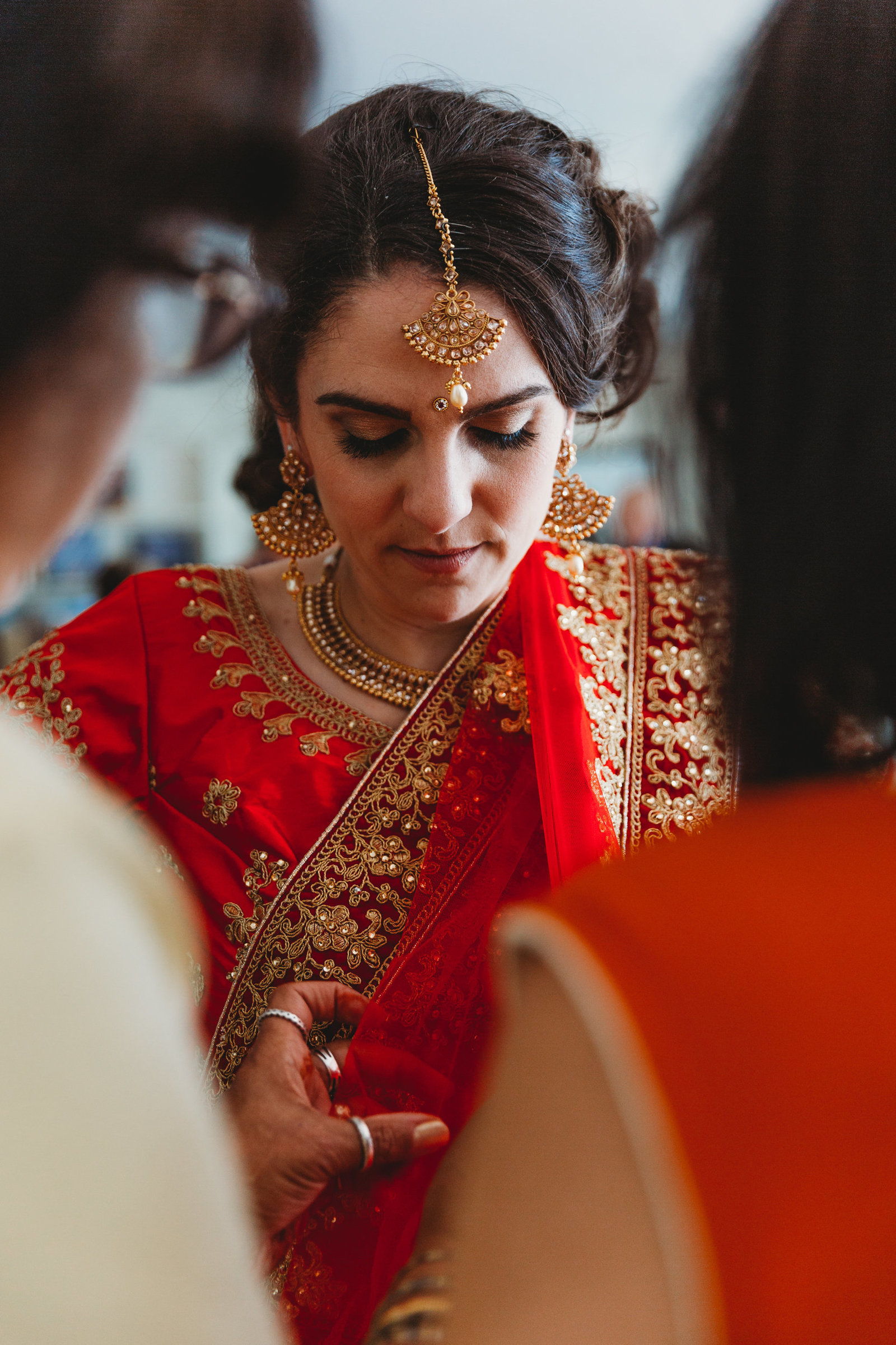 mothers adjust brides indian wedding robes before ceremony in massachusetts