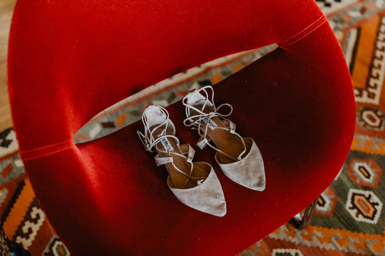 Strappy Steven Madden shoes are the perfect bridal shoe on this mid century modern chair at private Arkansas wedding