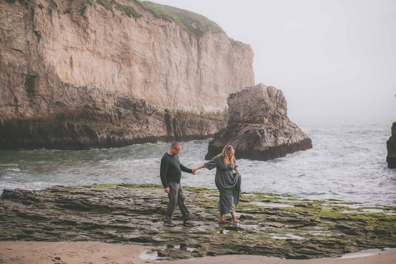 Couple hold hands and walk among rocky shoreline.
