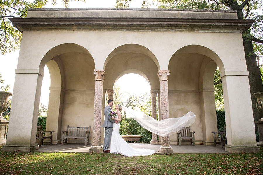 Bride and groom by arches at Gibraltar Garden