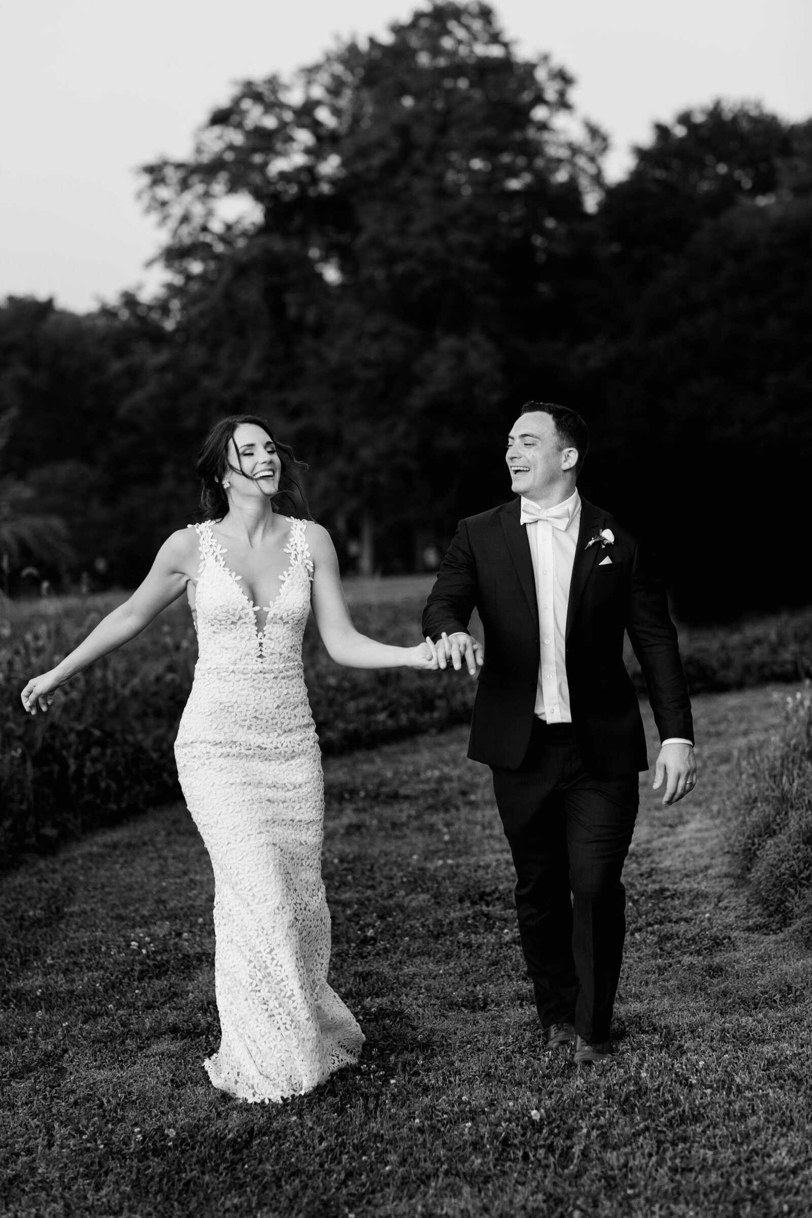 bride and groom laughing walking in field