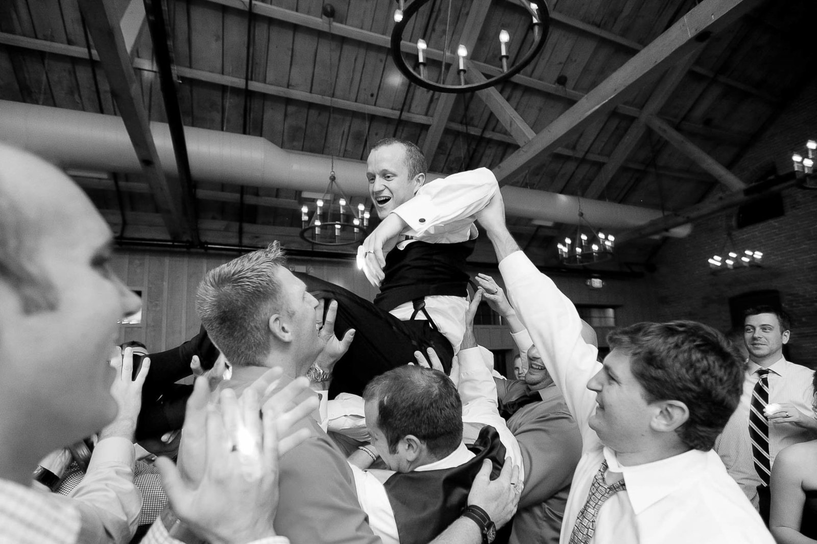 Groom is lifted by guests at reception, Cork Factory Hotel, Lancaster, Pennsylvania
