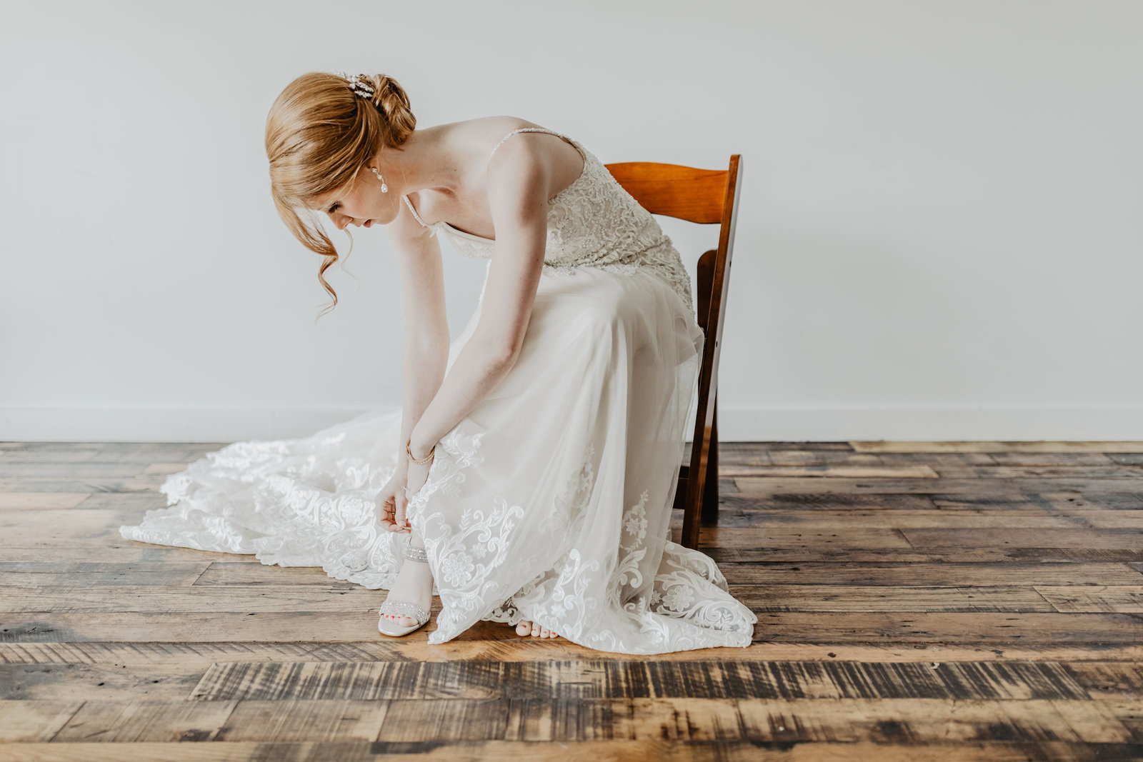 Bride sits and bends over to put on her shoes at Fat Bottom Brewery