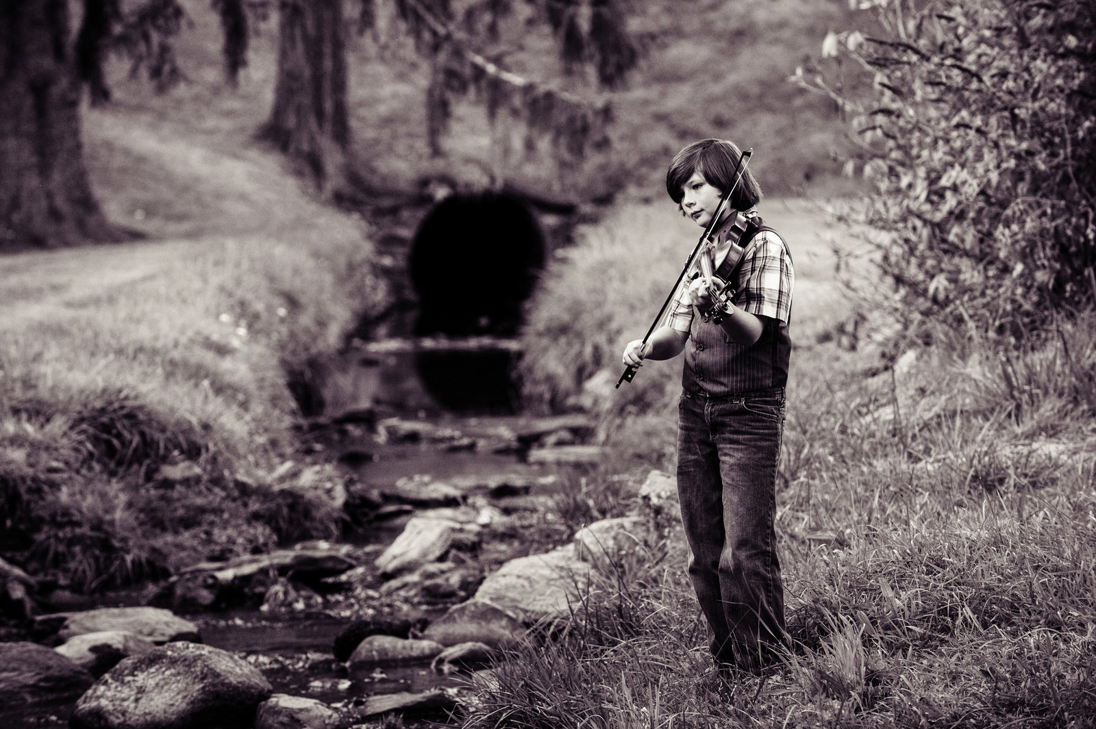 young liam purcell plays fiddle next to a stream in boone