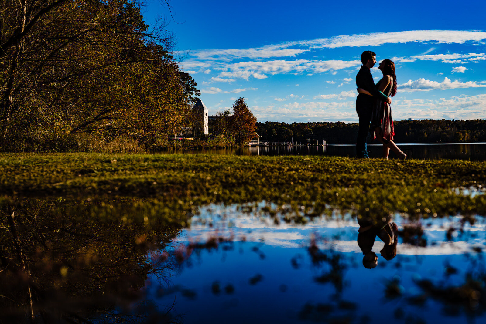 Couple poses next to Lake Crabtree during a Raleigh engagement photo session