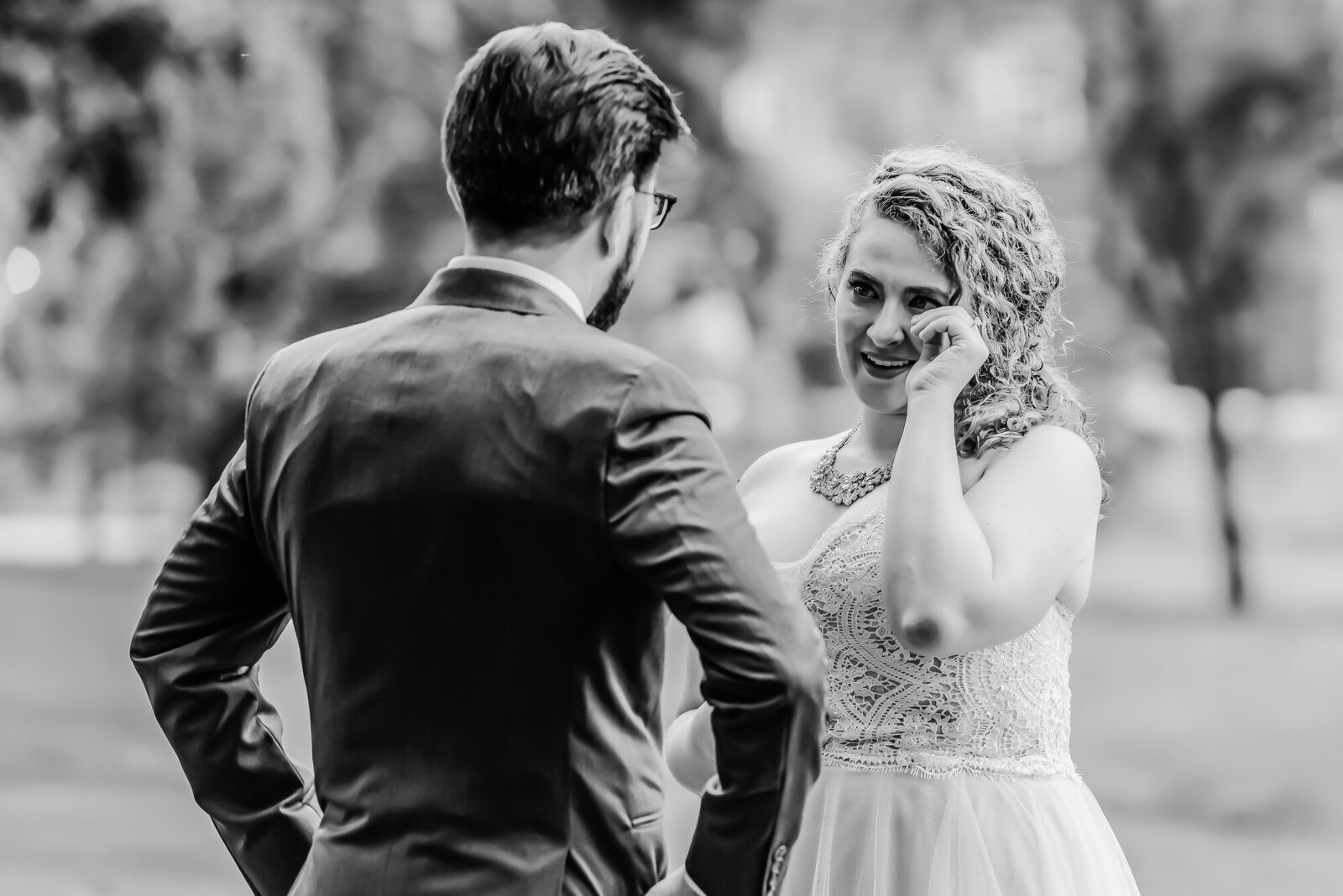 Black and white candid photo of an emotional first look between a bride and her groom before their wedding