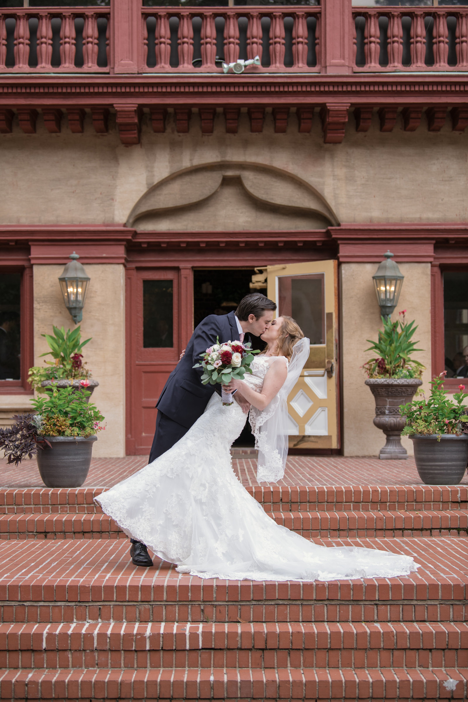bride and groom kissing photo in front of Coindre Hall