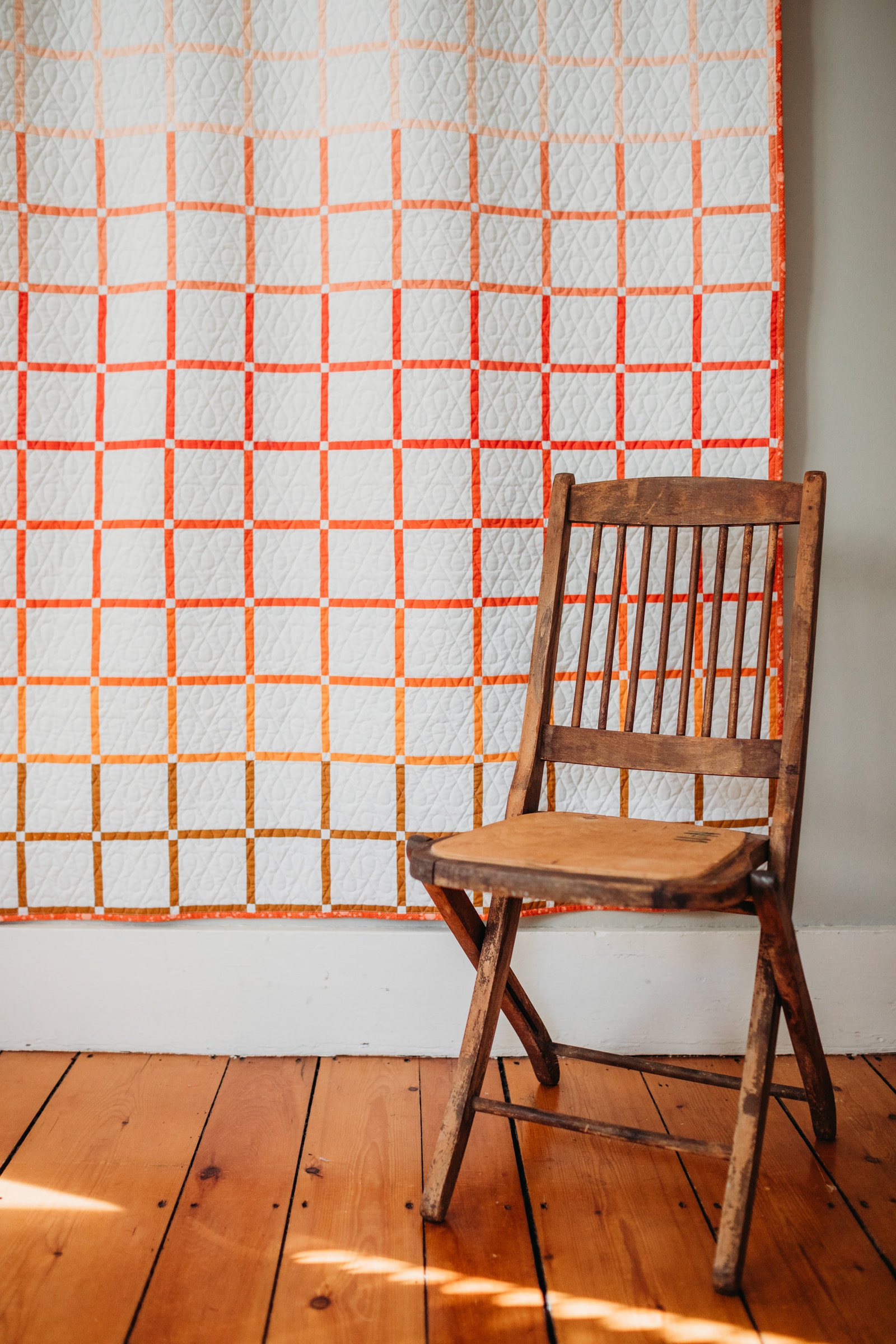 wooden antique chair in front of hanging pink square quilt