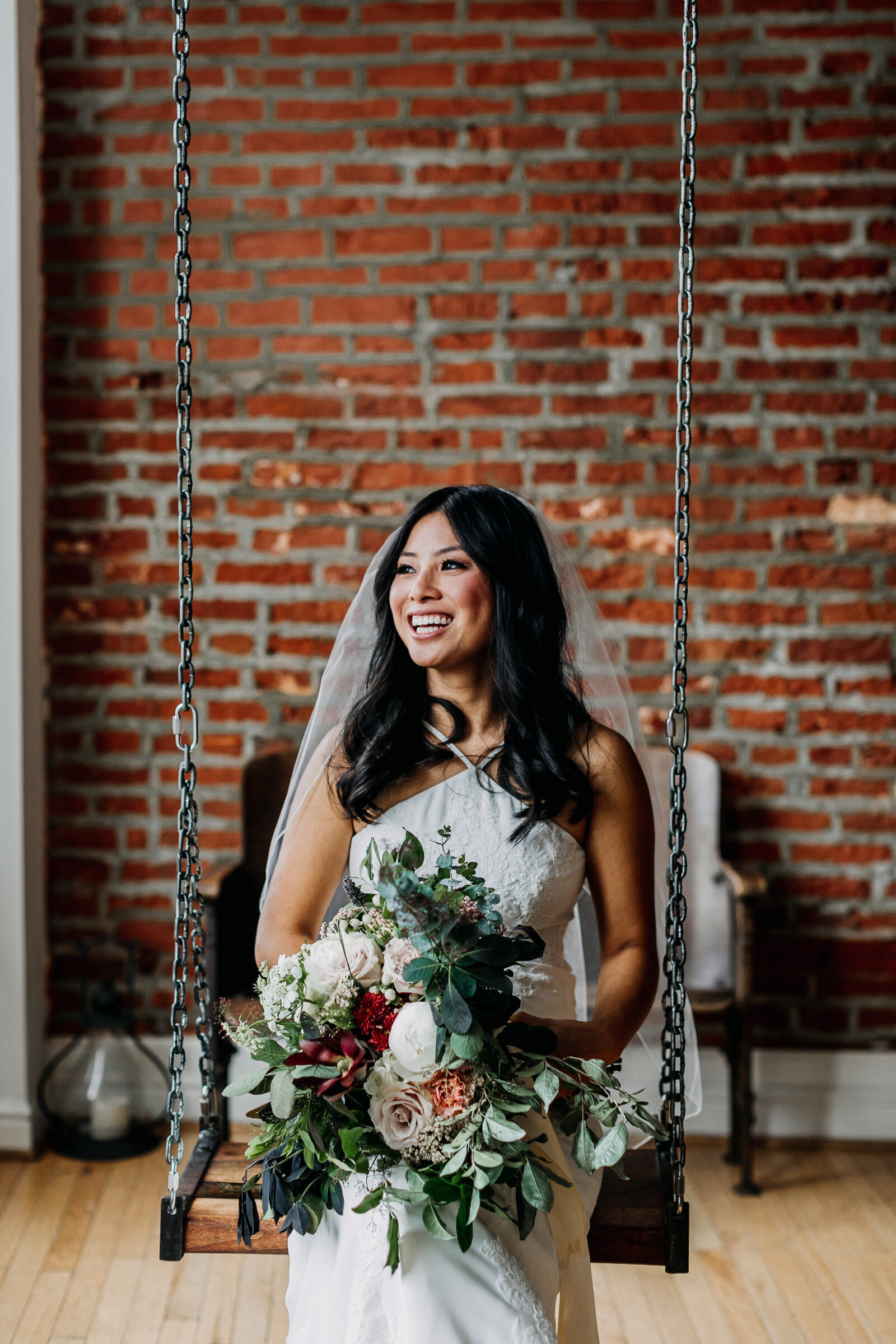 bride with bouquet sitting on swing with brick wall