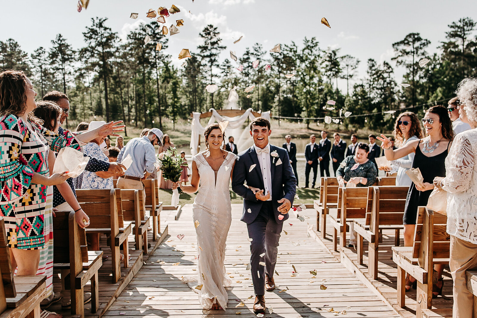 Guests throw flower petals as the Bride and Groom exit their ceremony at their Griffin, Ga wedding
