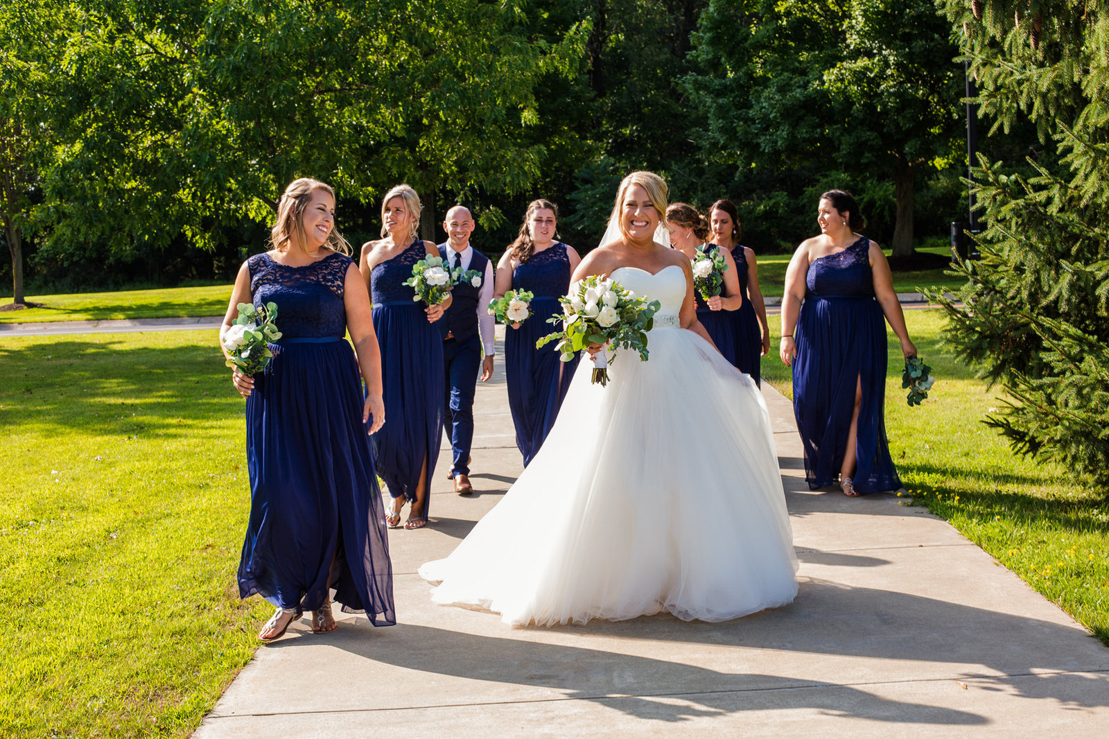 Bride walks with her bridal party along a path on the campus of Edinboro University