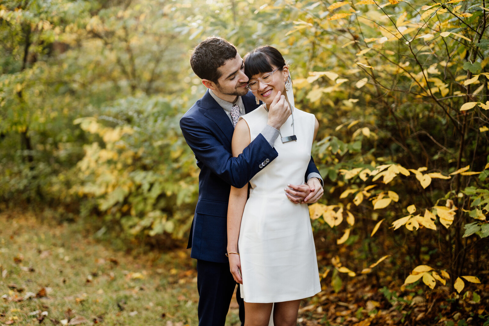 bride and groom hugging in fall leaves