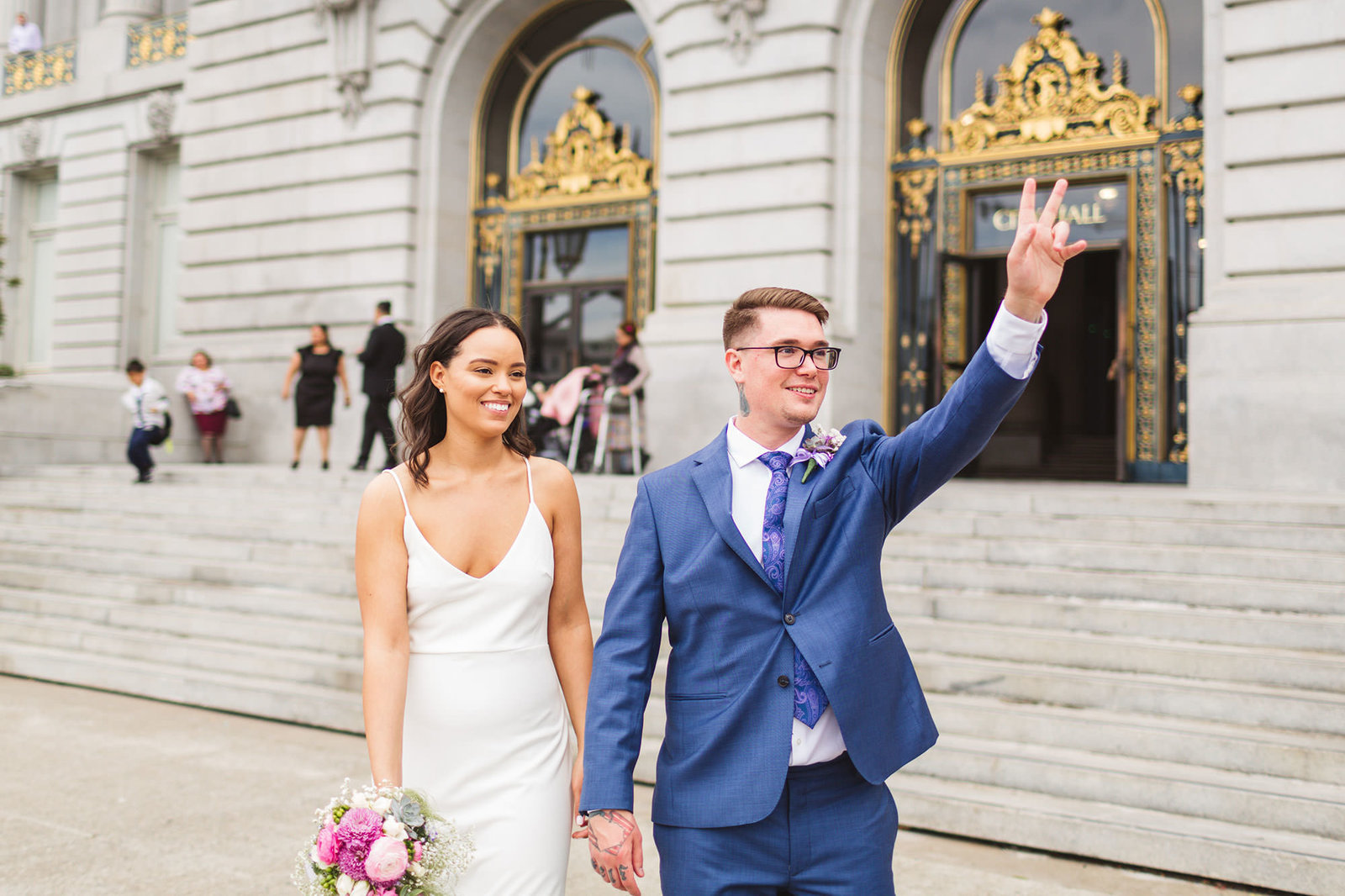 newlywed couple hailing cab outside san francisco city hall