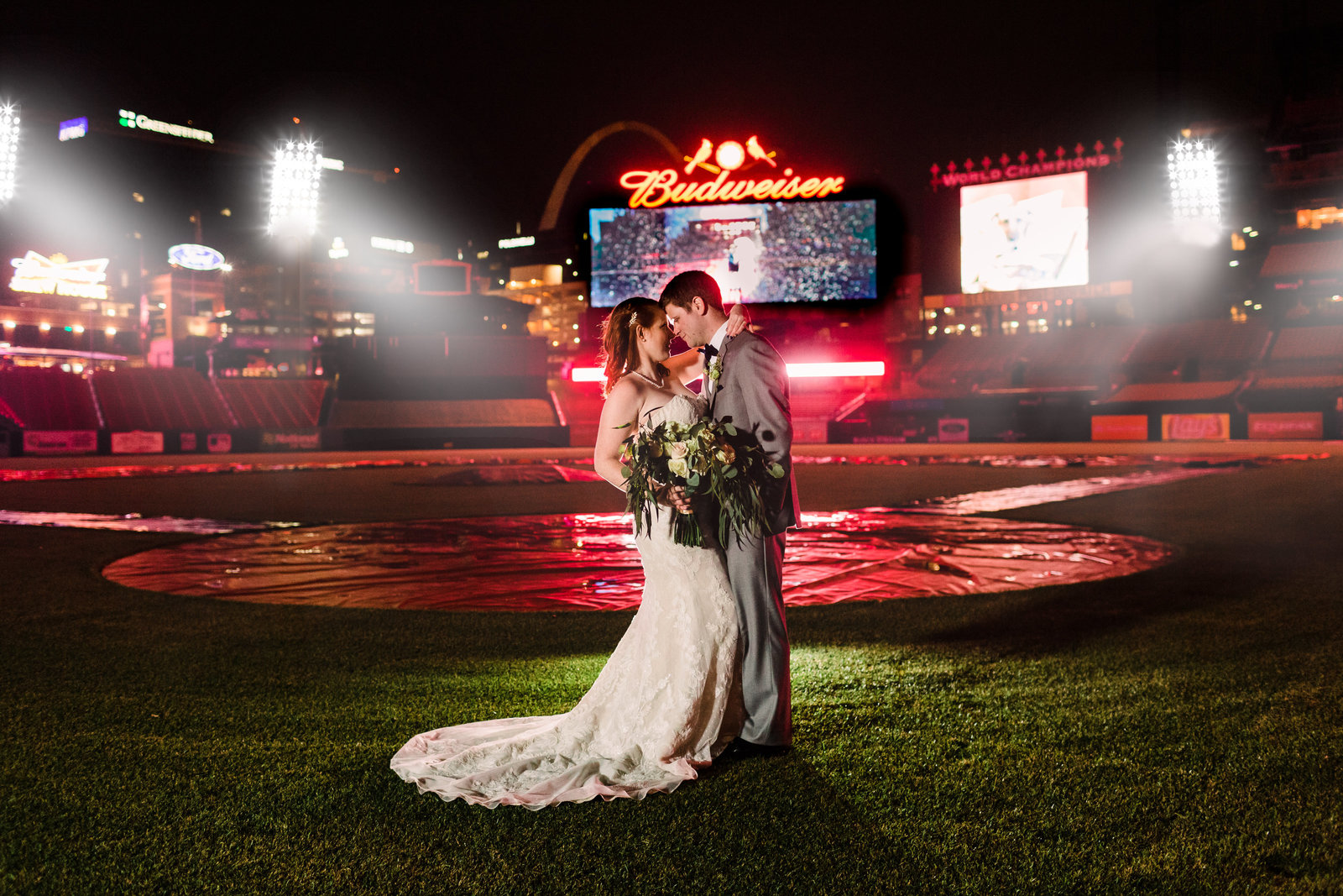 Bride and Groom, Kailyn and Adam, face each other to kiss on the field of Busch Stadium under the stadium lights.