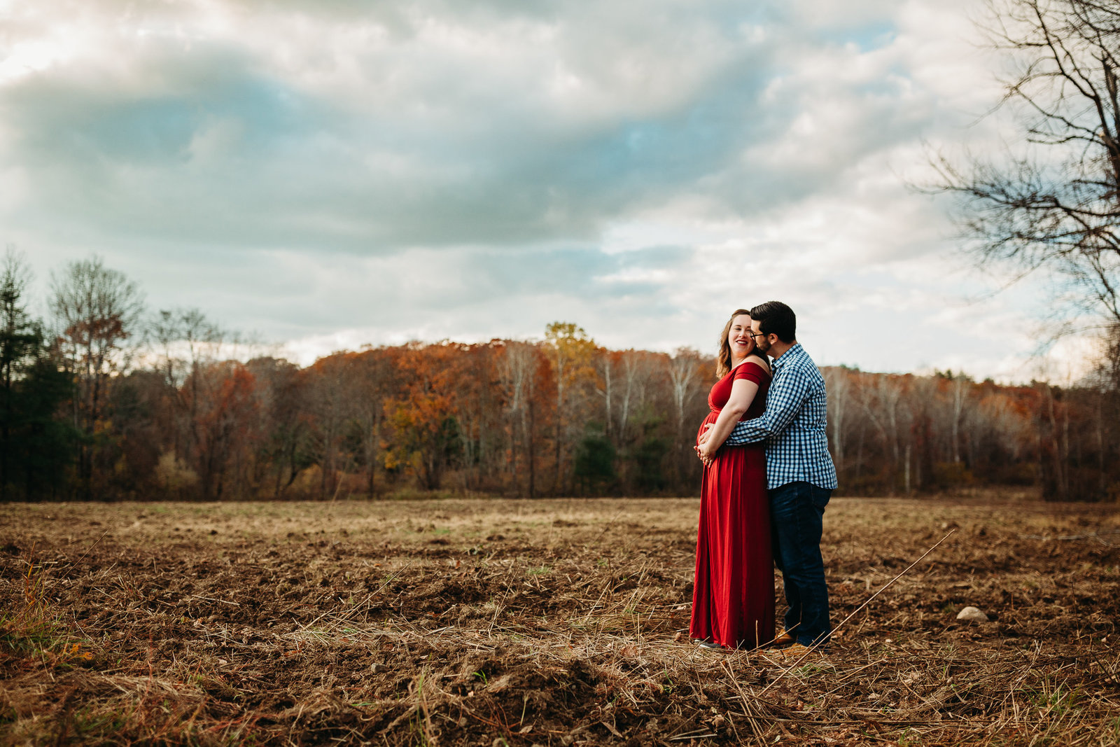 expectant mother in red dress stands in field with father in framingham ma