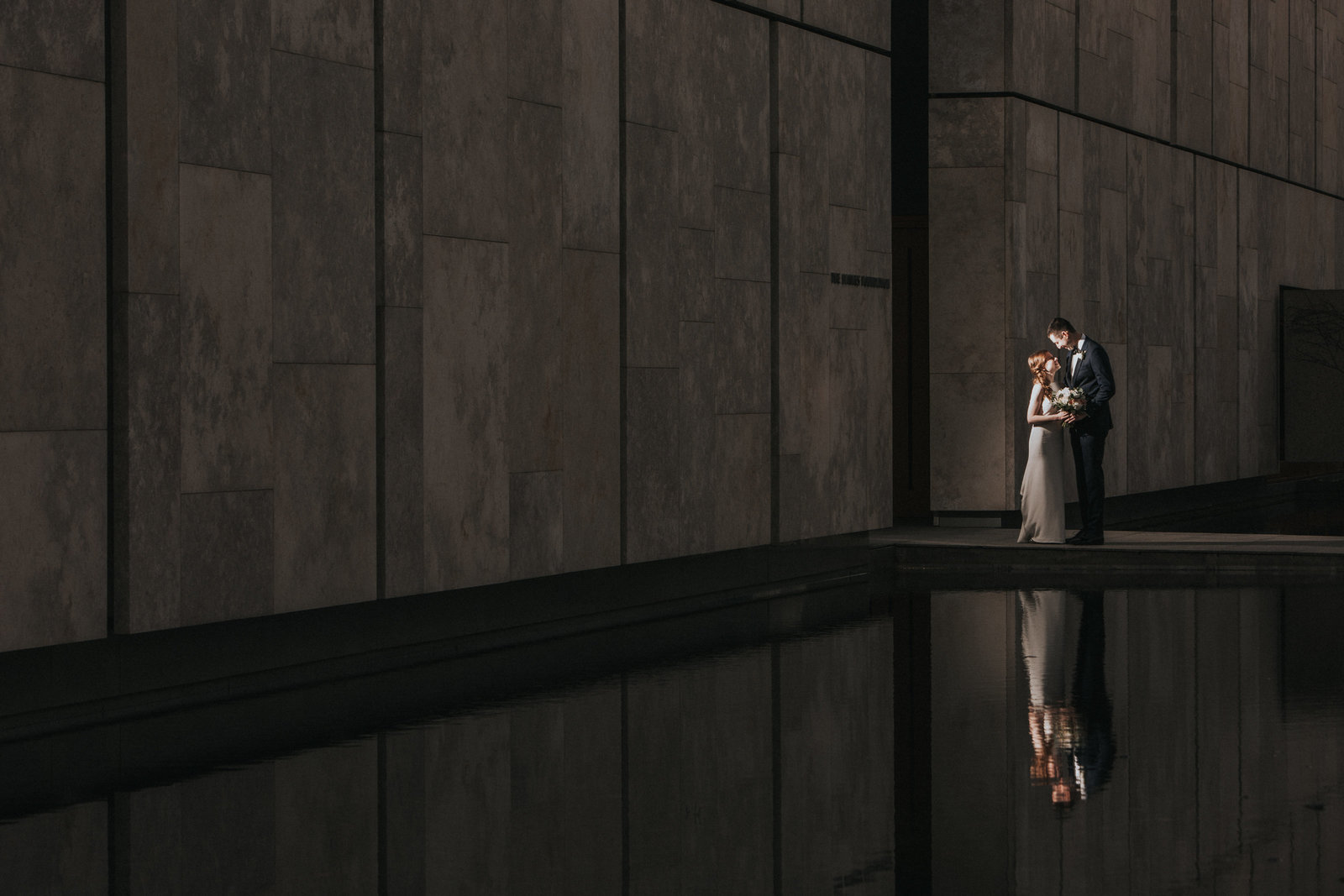 bride and groom portrait in front of the water at the barnes foundation