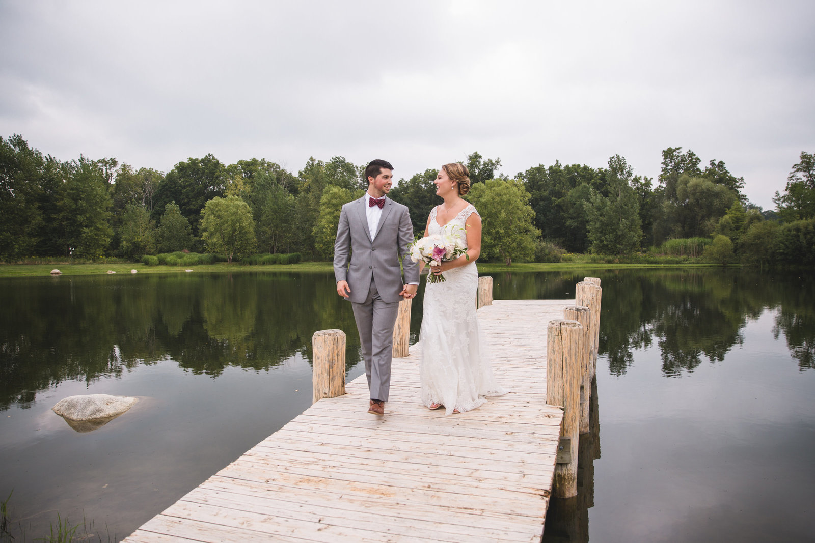 bride and groom at end of dock in michigan