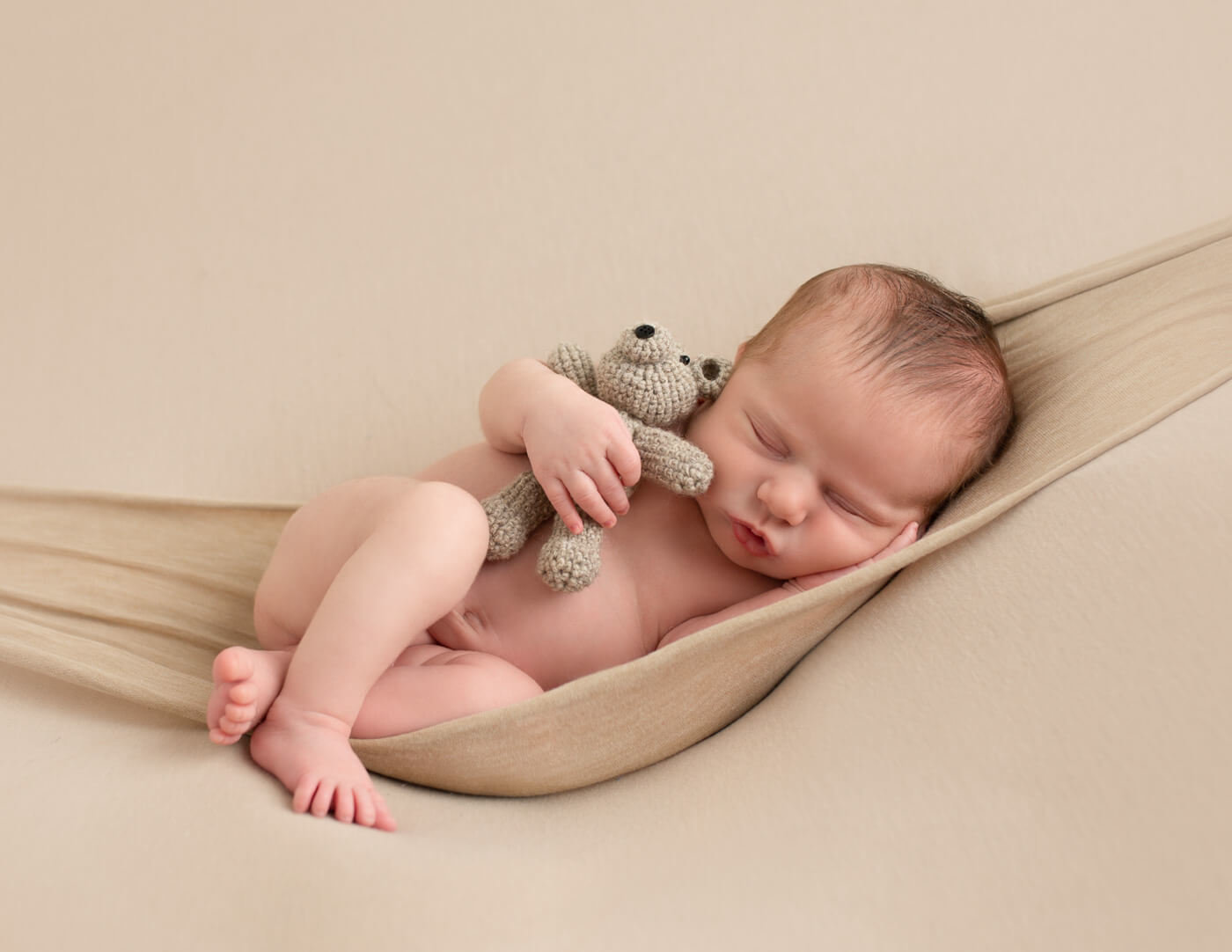 Newborn baby boy posed in a hammock in our Rochester, NY studio.