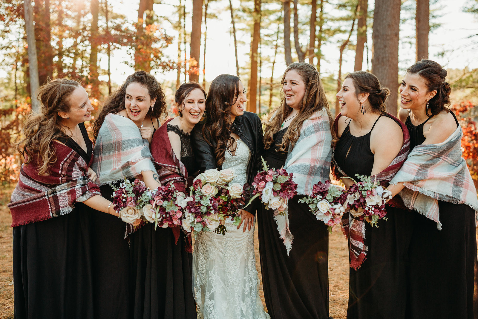 bride and bridesmaids laugh while wrapped in shawls at outdoor massachusetts autumn wedding