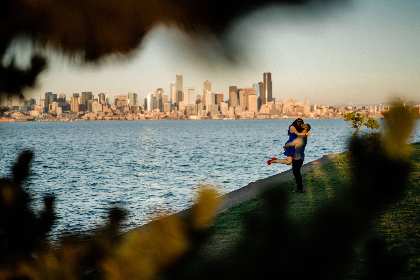 Trees and Puget Sound frame the skyline for this couple's engagement pictures at Alki Beach, the best spots for engagement photos in Seattle