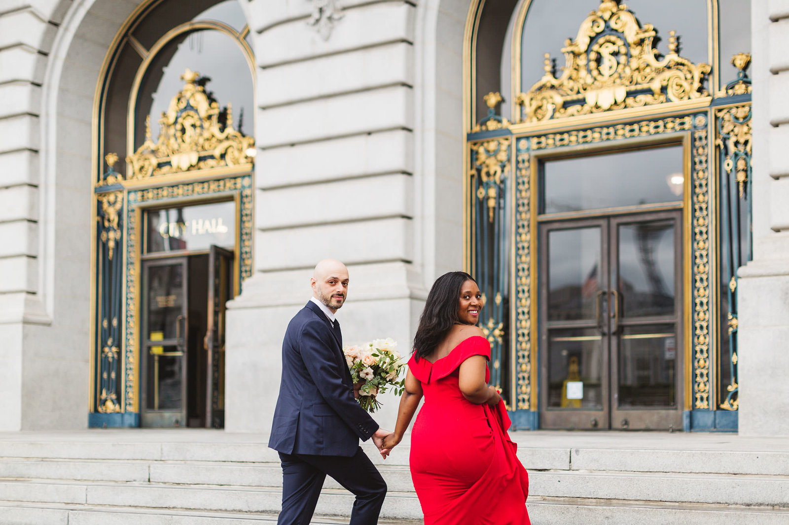 cute swirl couple walking up the steps of city hall before their elopement ceremony