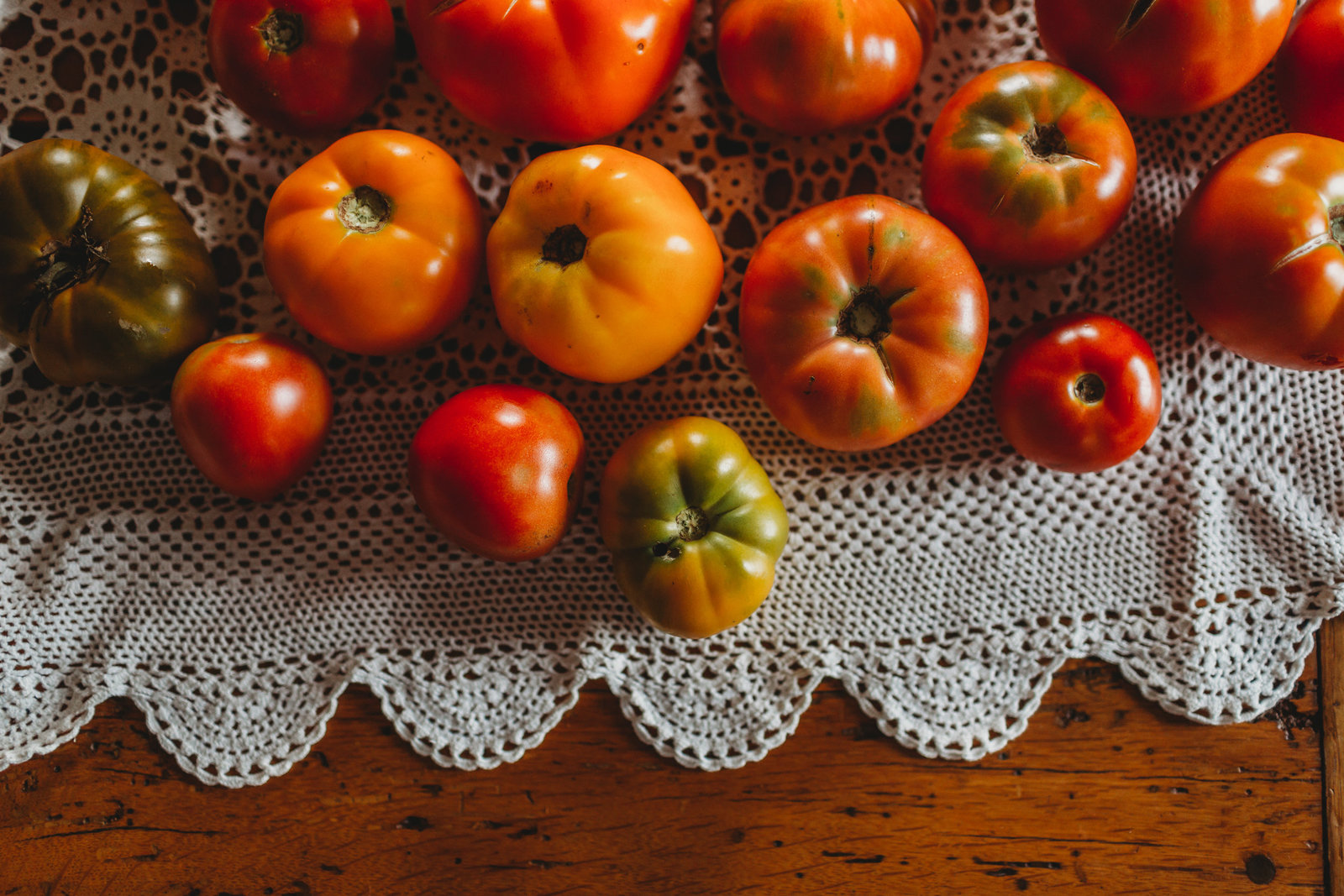 ripe tomatoes are scattered on a lace tablecloth