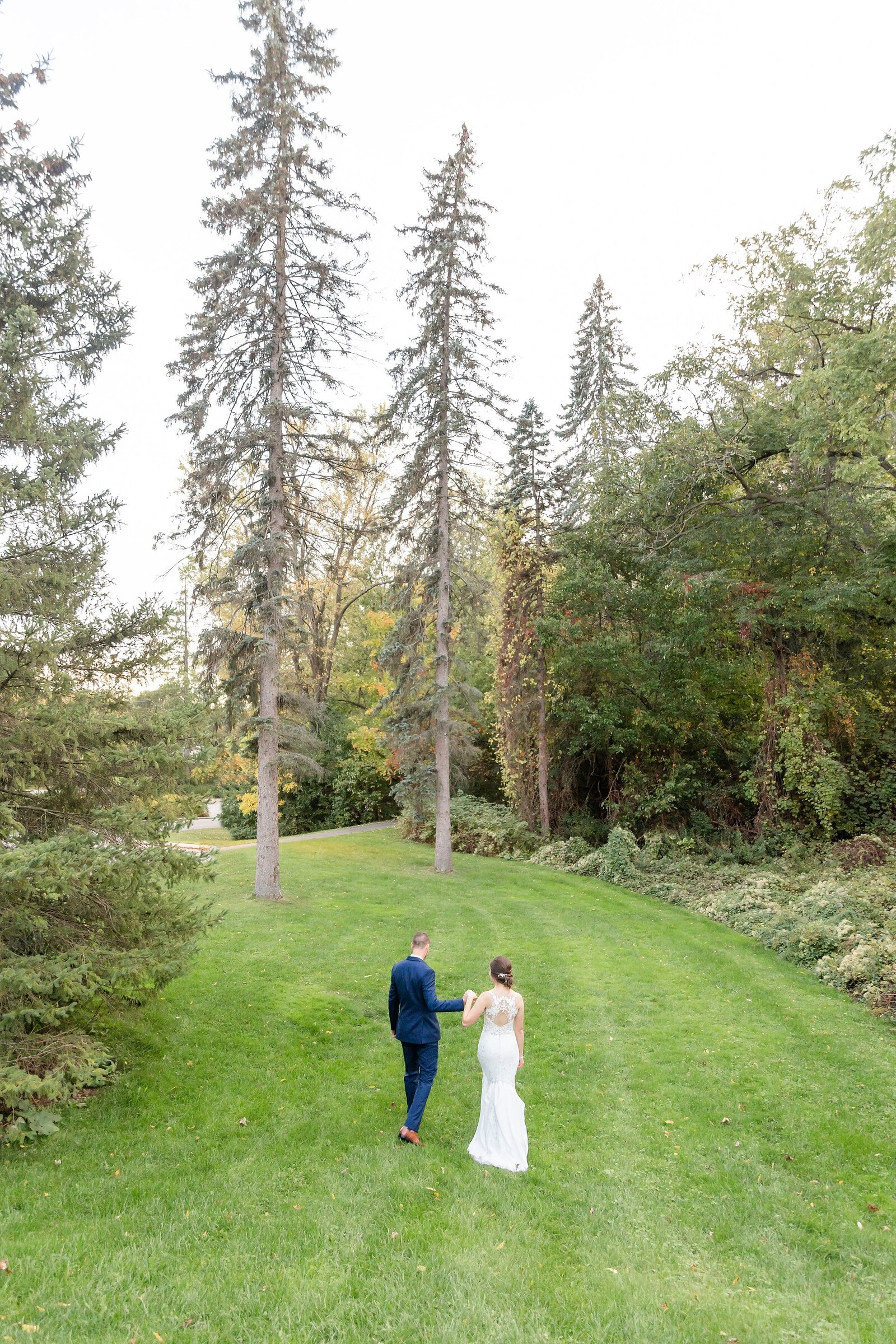 Couple-walks-away-down-a-hill-towards-beautiful-towering-trees-at-windermere-manor-in-london-ontario