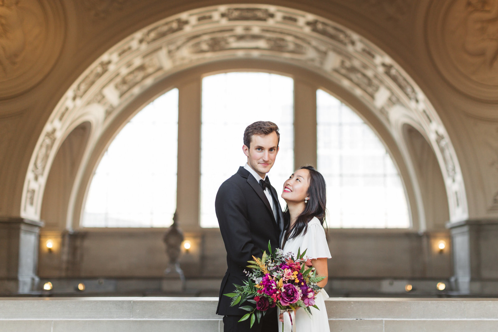 san francisco city hall wedding couple framed by arch on 4th floor