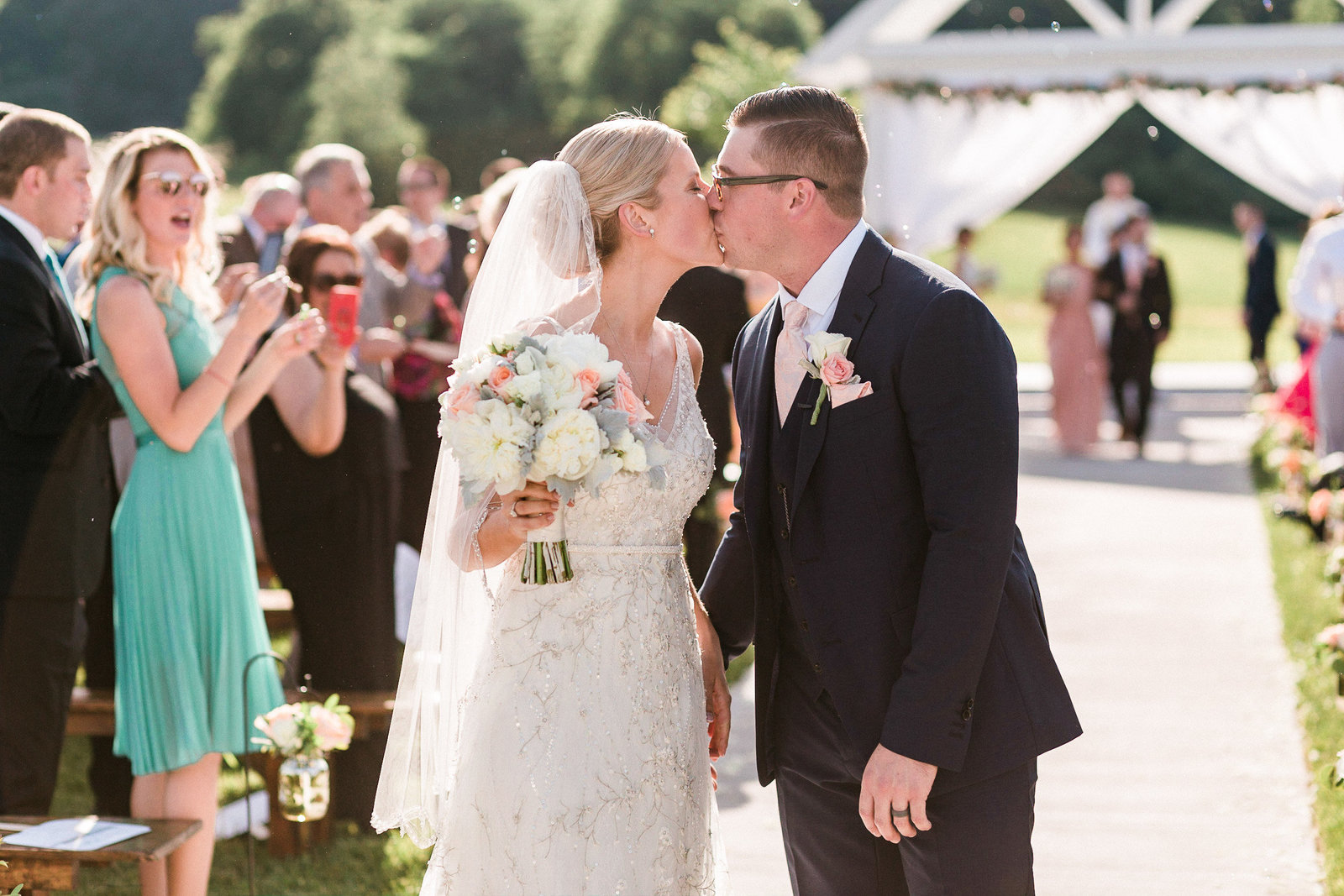 Bride and groom kiss while walking down the aisle at Springfield Manor Maryland