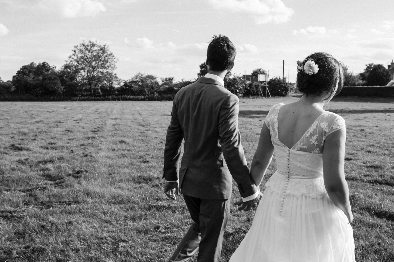 Black and White photograph of relaxed natural newlyweds walking in to the sunset after their wedding ceremony in the suffolk countryside