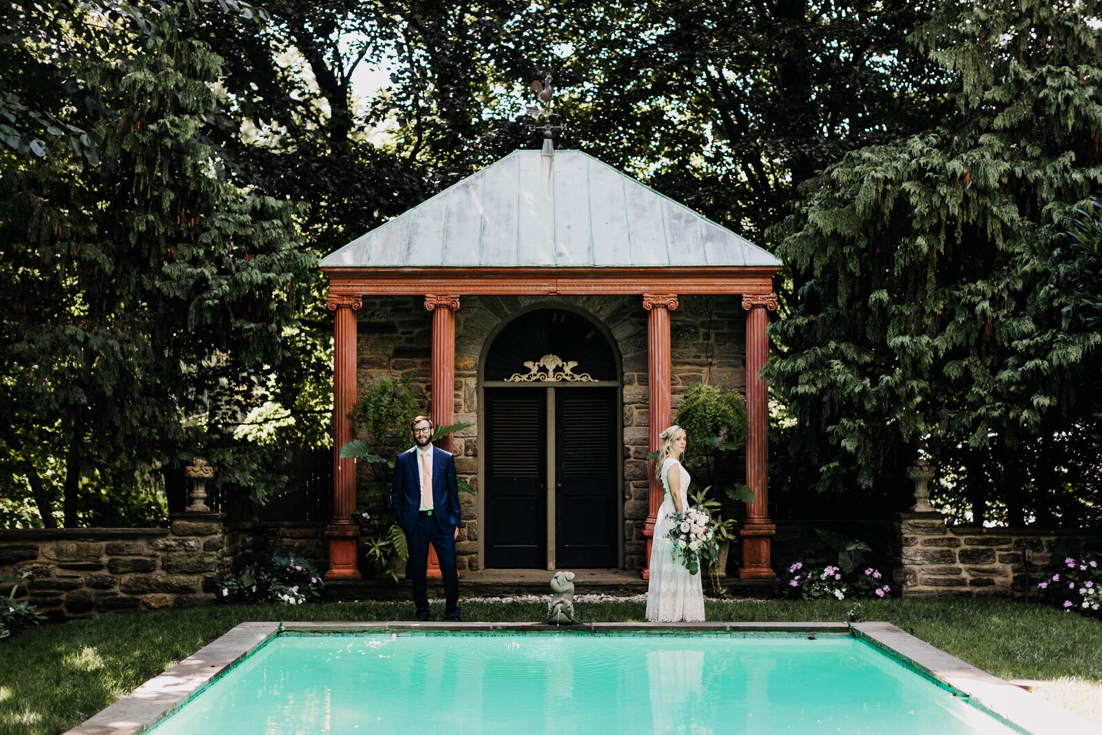 bride and groom in garden with pool