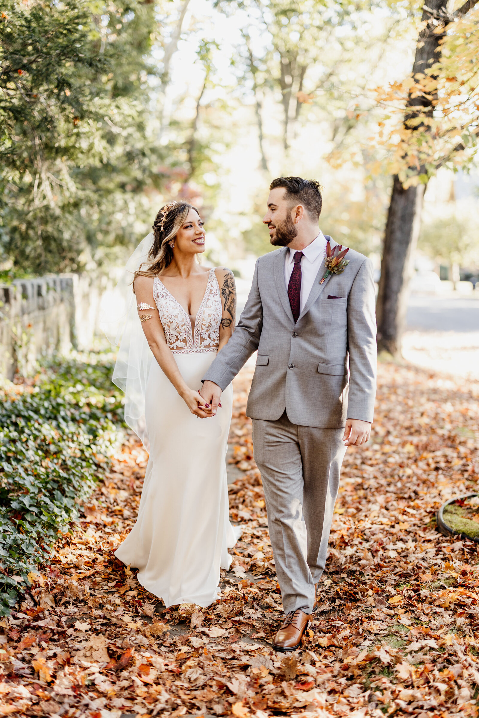 bride and groom walking in fall leaves