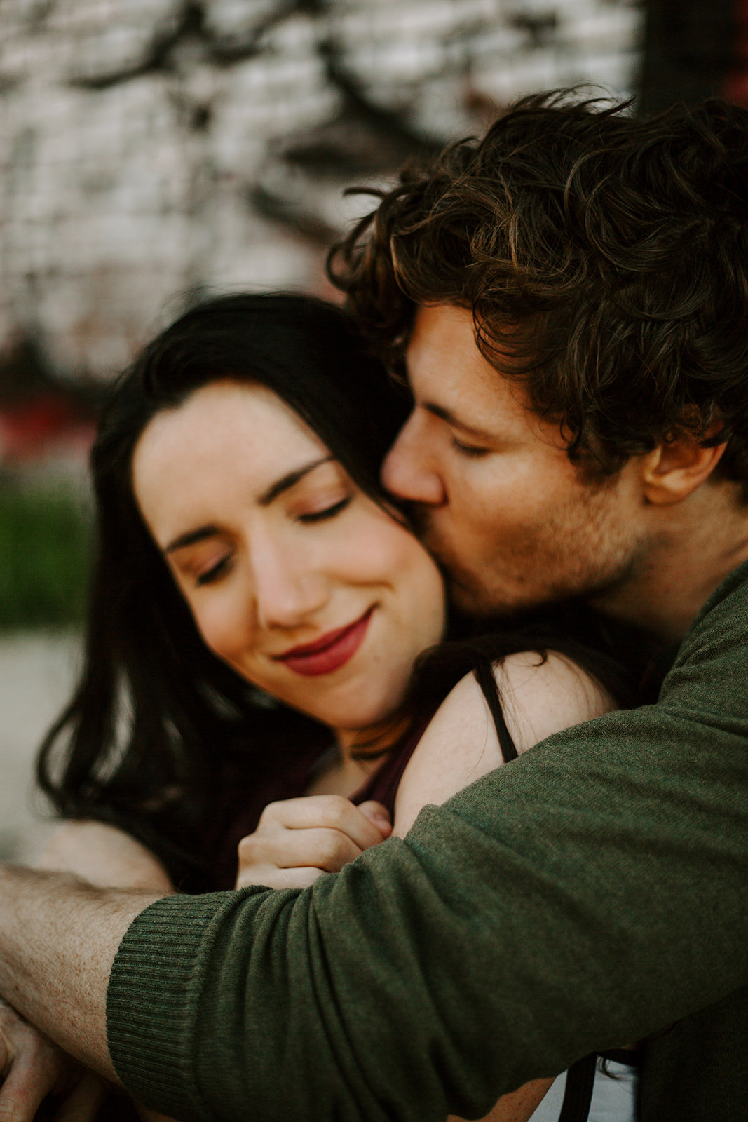 Man kissing his girlfriend on the cheek during his Minneapolis engagement session
