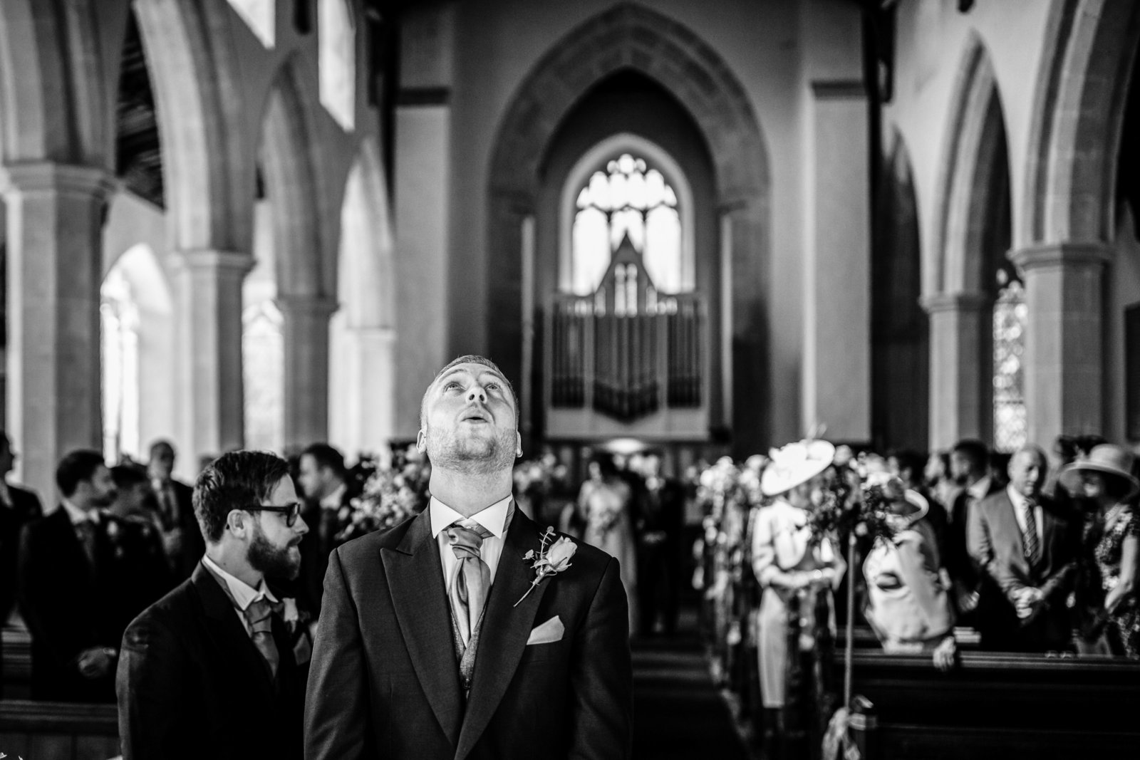 Nervous Groom waits at altar for Bride to arrive, he looks up to ceiling nervously in a traditional Norfolk church.