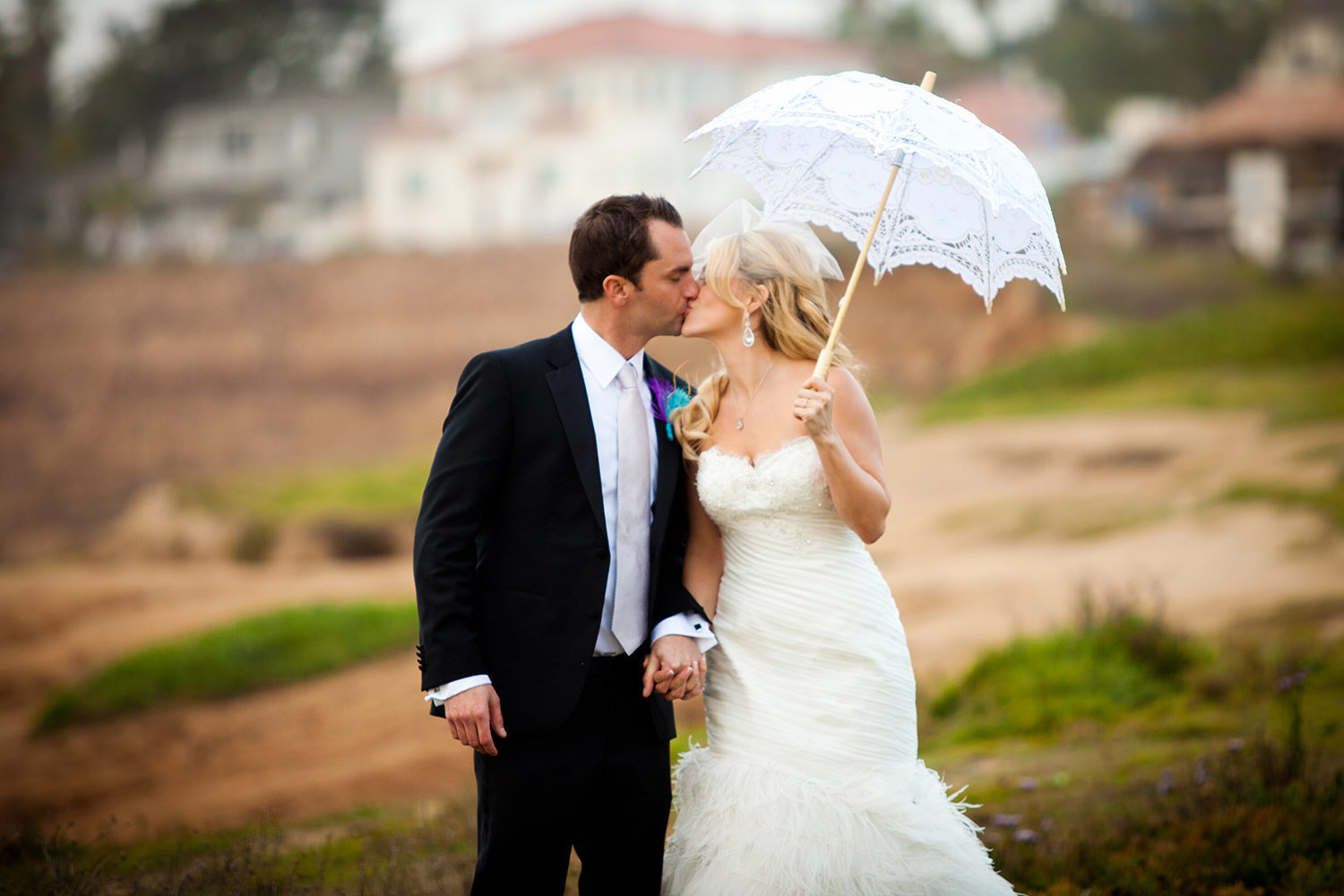 bride and groom with umbrella at beach