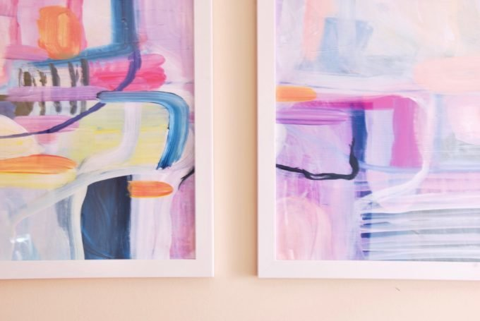 Two white framed pieces of colorful abstract art.