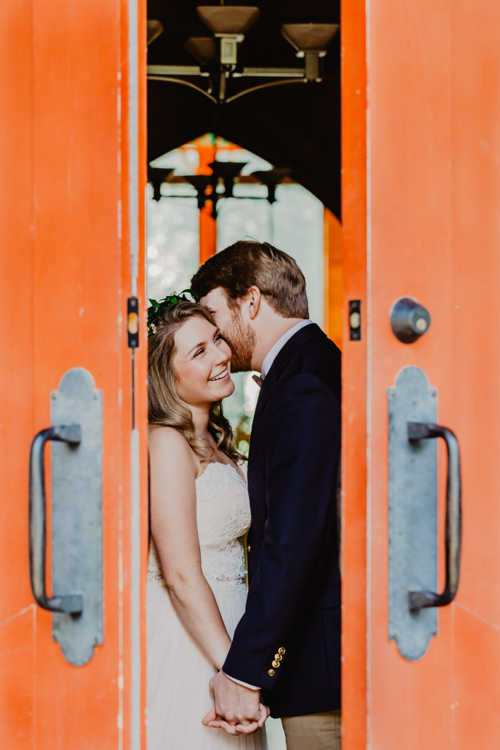 With the doors cracked Groom leans down and whispers in Brides ear.