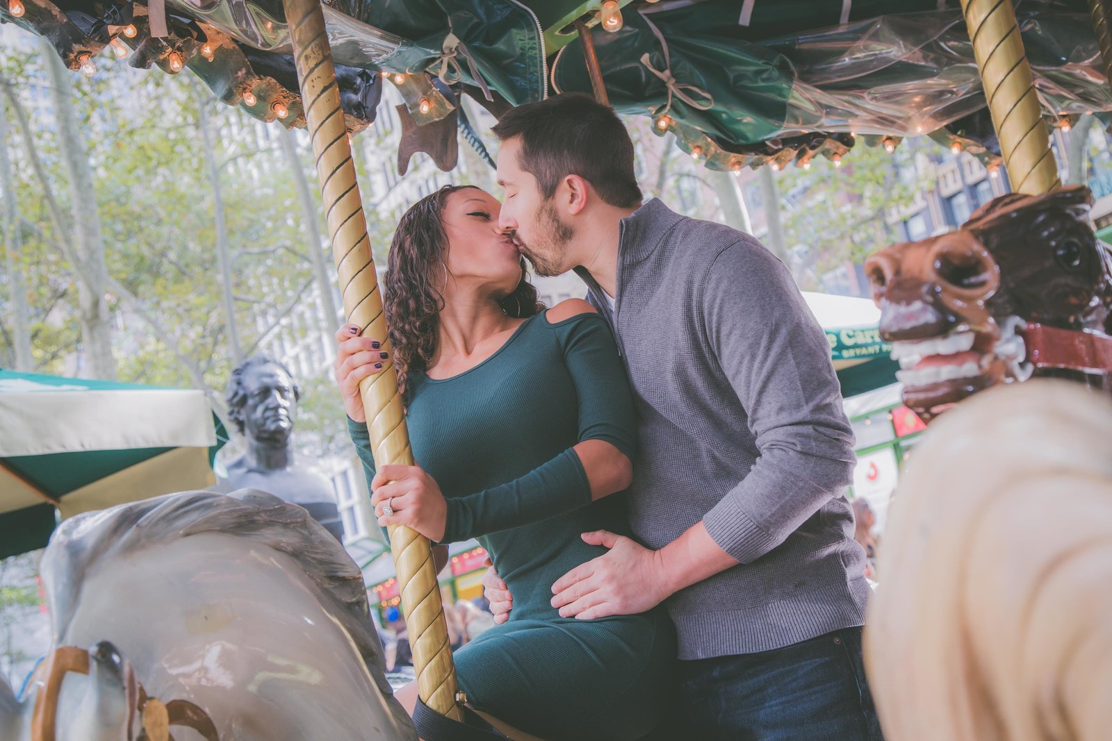 Couple kisses on Bryant Park NYC carousel.