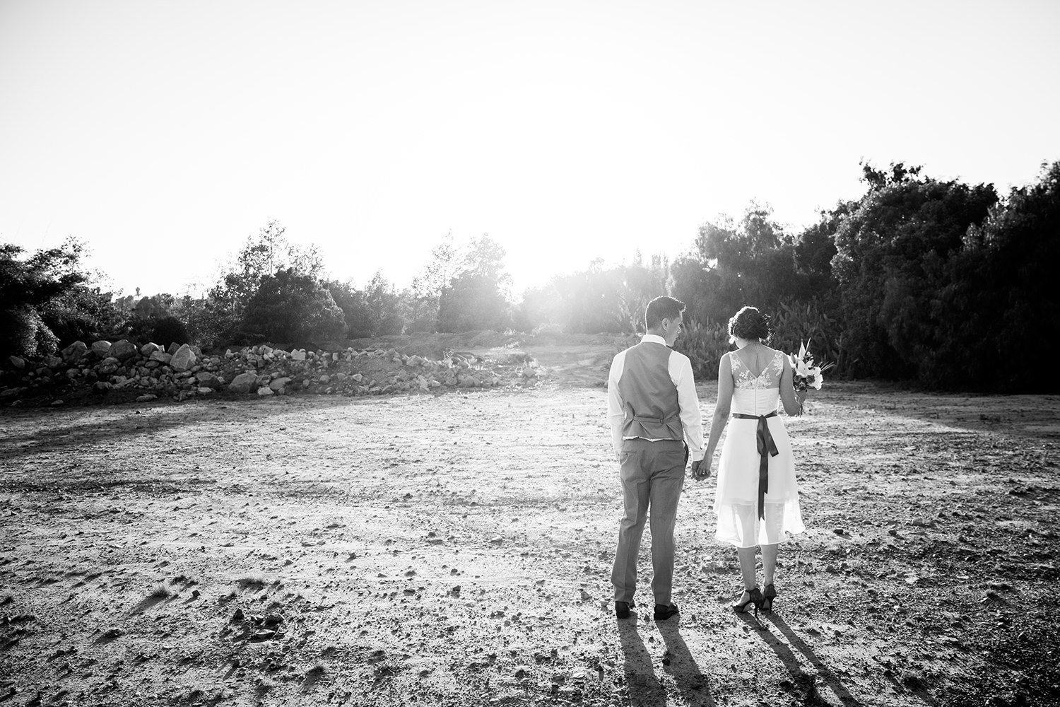 Black and white wedding portrait composed with the sunset