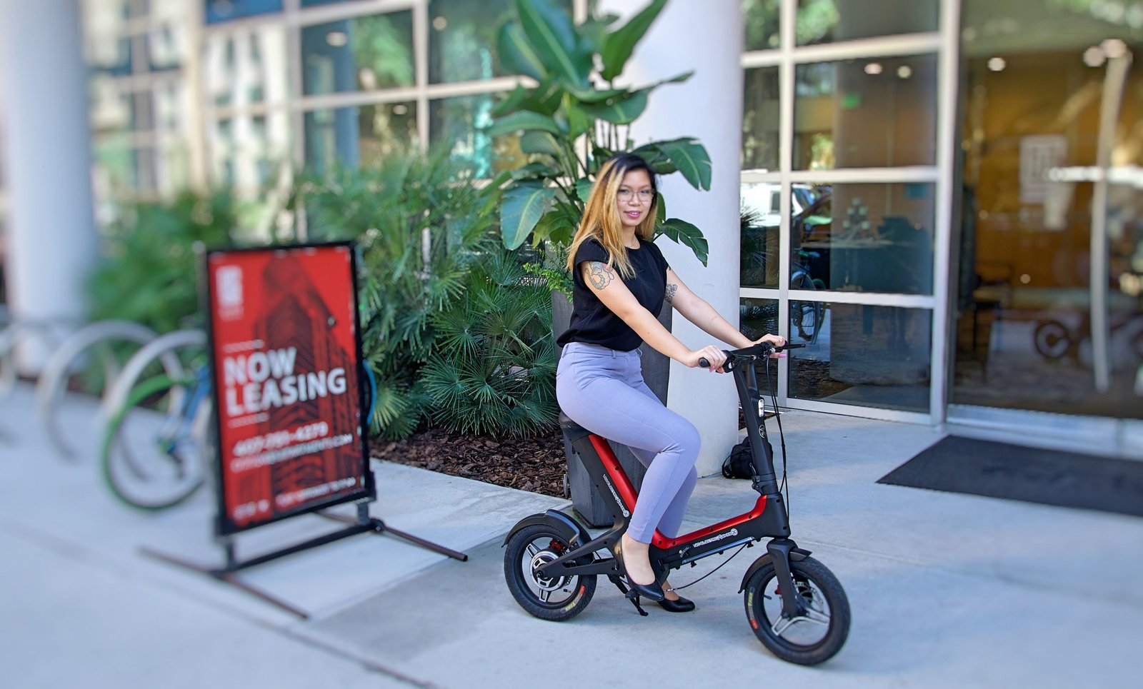 Lady on Red Go-Bike M3 in front of leasing office