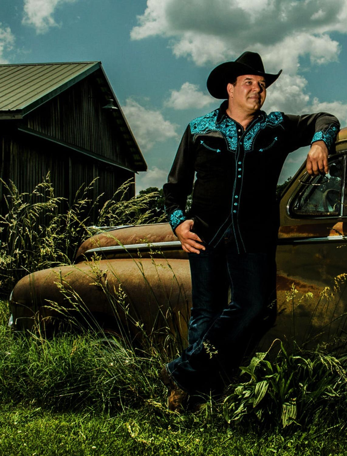 Interview featuring Mark Maryanovich country music photography South 40 musician in cowboy hat leaning against vintage car parked in grass barn and blue sky with puffy clouds behind him page 7