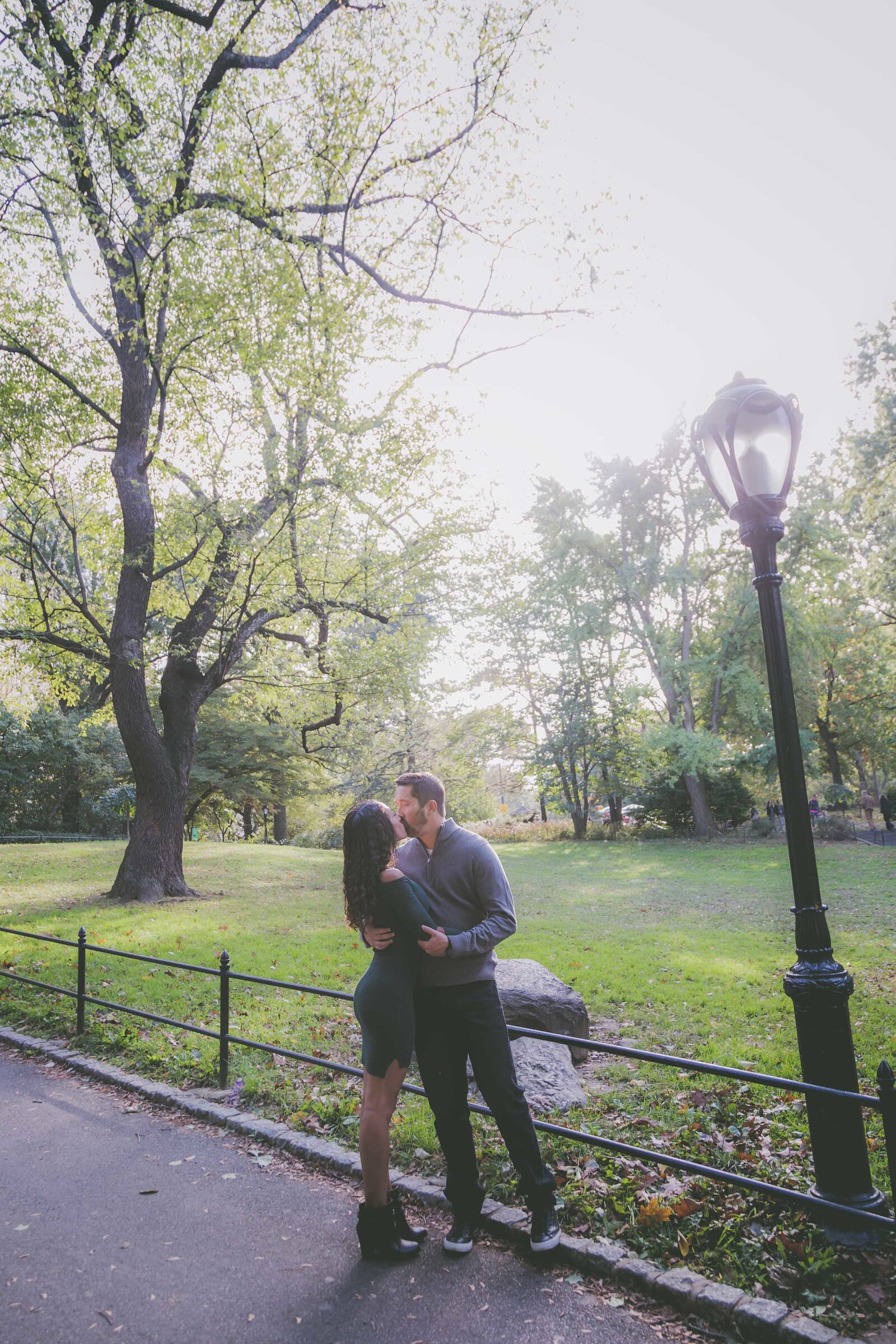 Couple kisses in Central Park during their engagement.