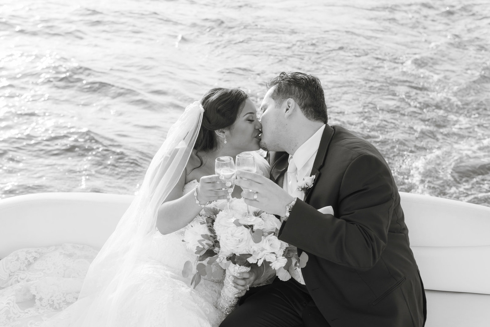 Bride and groom kissing on boat at Chateau La Mer