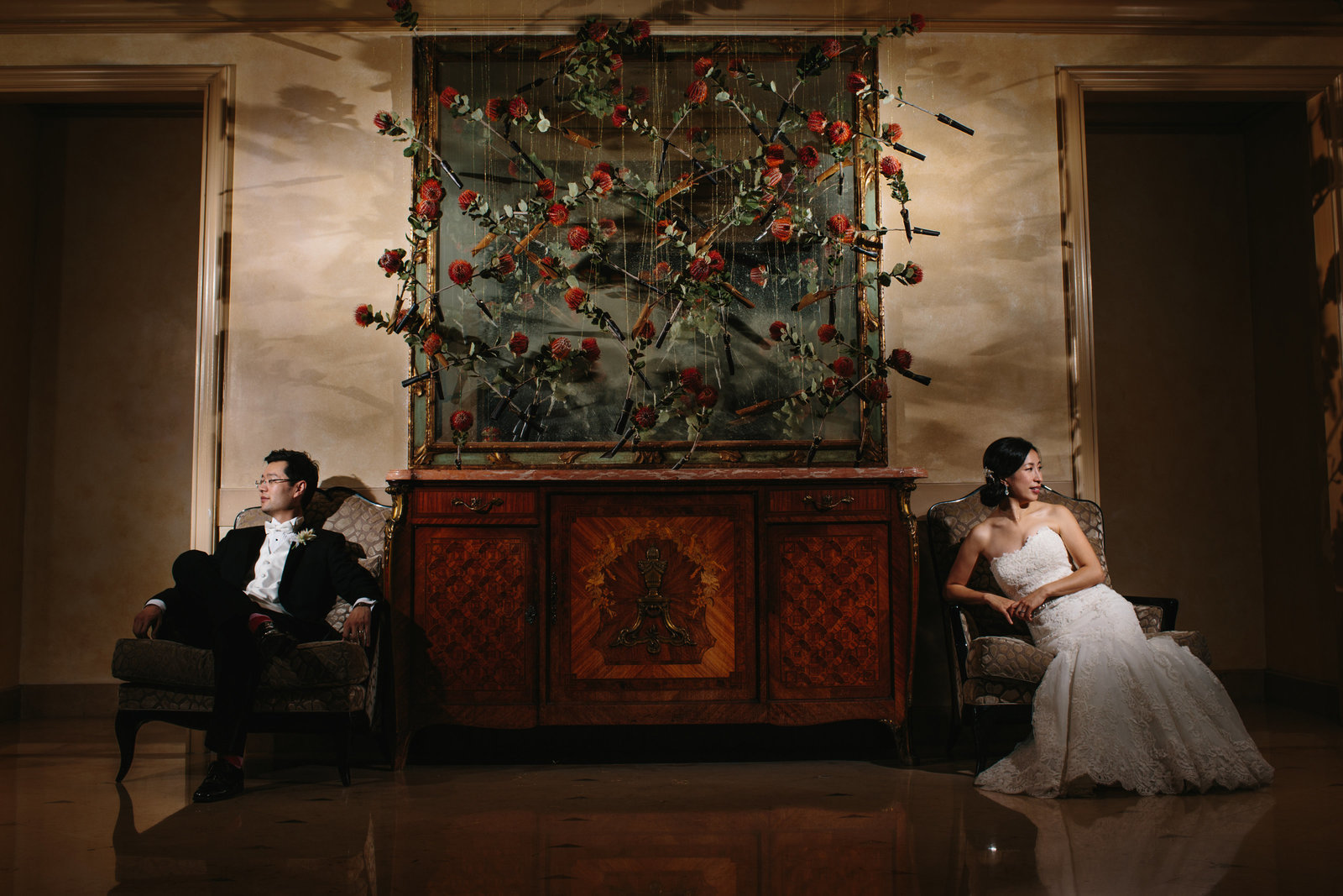 Dramatic bride and groom photo  in hotel lobby sitting on either side of hanging flowers