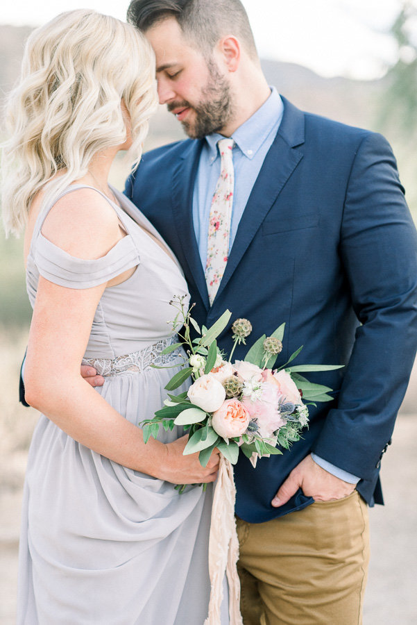 Tucson Desert Engagement Session Photo of Couple Nuzzling with Bouquet | Tucson Wedding Photographer | West End Photography