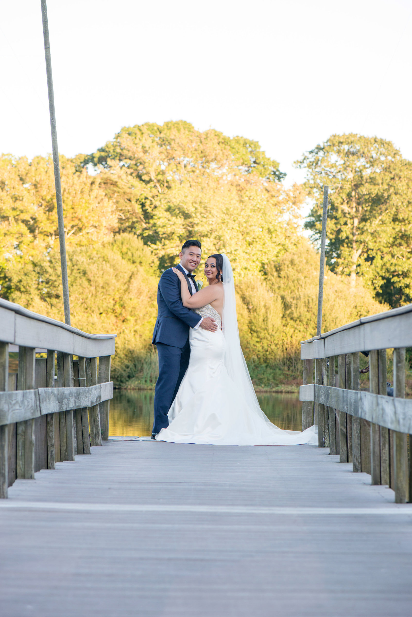 Bride and groom smiling on dock at Camp Pa-Qua-Tuck
