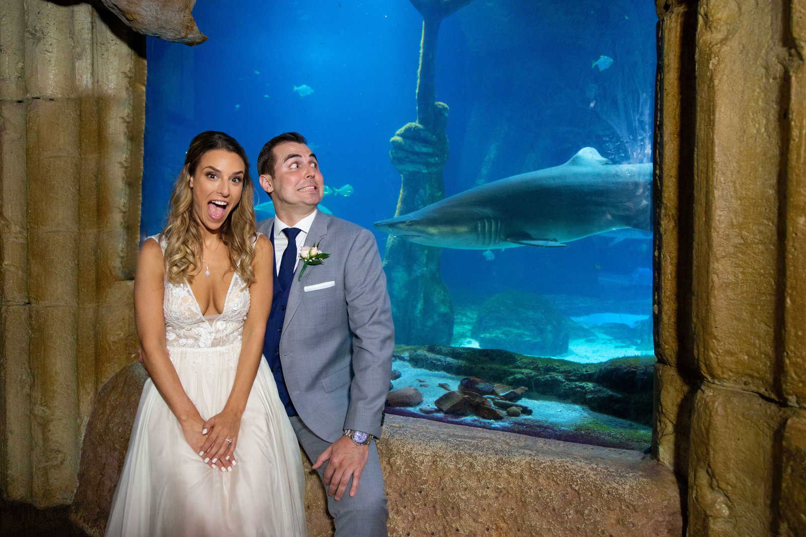 Bride and groom in front of sharks at Atlantis Banquet and Events