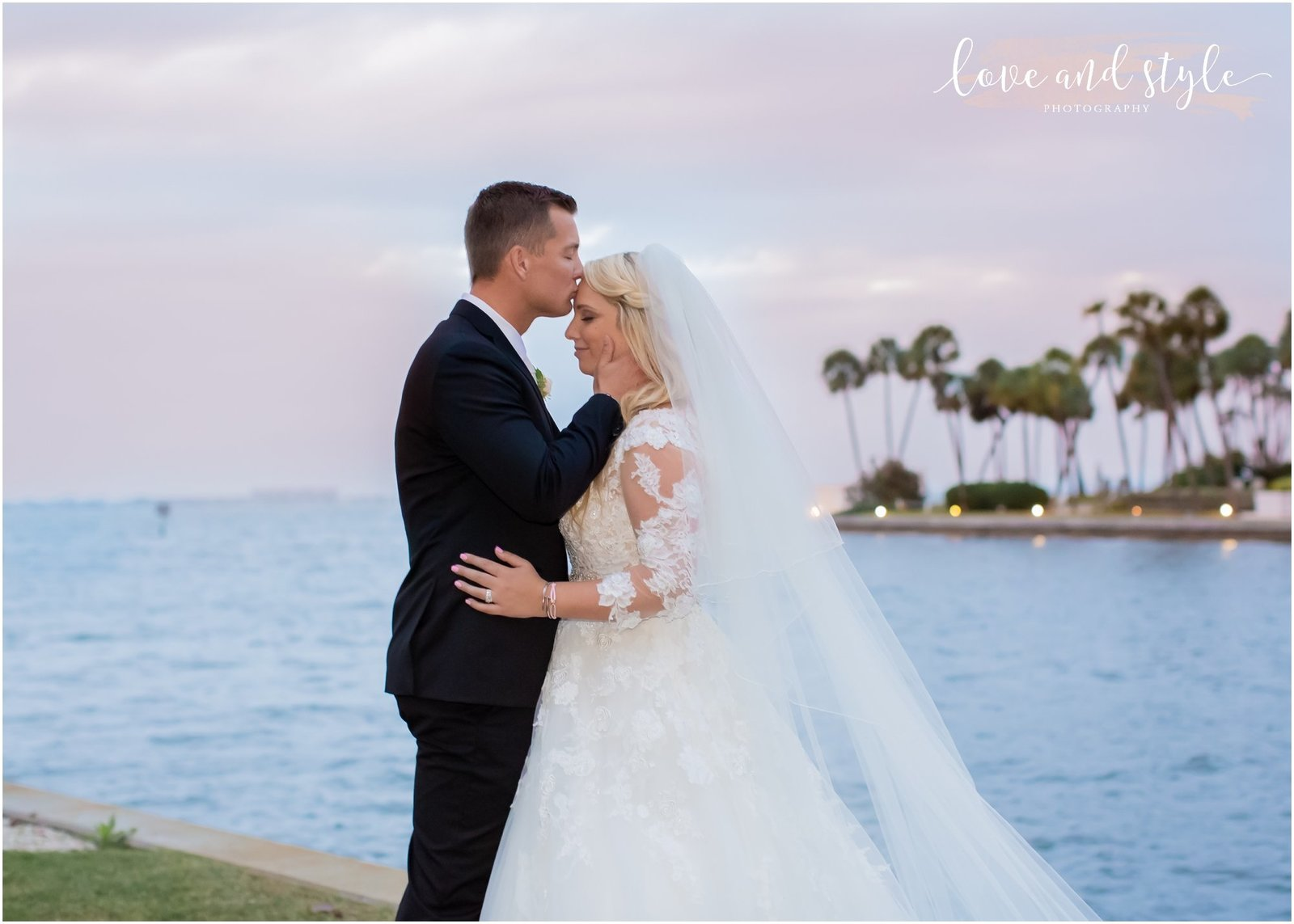 Bride and Groom embracing at the water's edge at The Ritz Carlton, Sarasota